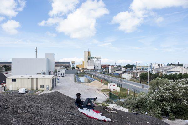 CALAIS – FRANCE – 1er juillet 2017 : Un jeune réfugié se repose sur un tas de gravats d'une entreprise à deux pas de l'ancienne jungle de Calais.