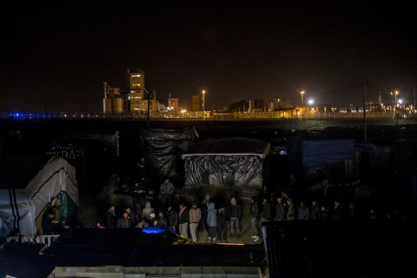 Migrants waiting outside the Belgium Kitchen dinner. About 800 meals are distributed each evening by the volunteer kitchen. In Calais, northern France, February 23, 2016