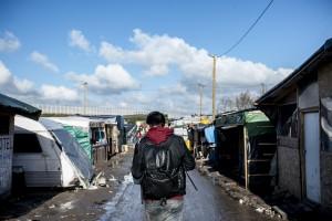 Un réfugié marche dans l'avenue principale de la jungle de Calais