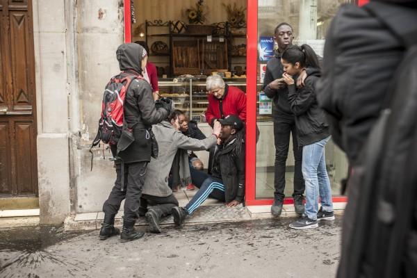 Un jeune fille gazée est soutenue par d'autres lycéens et la boulangère