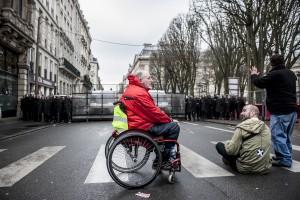 Une personne handicapée reste campée devant la police en fin de manifestation.