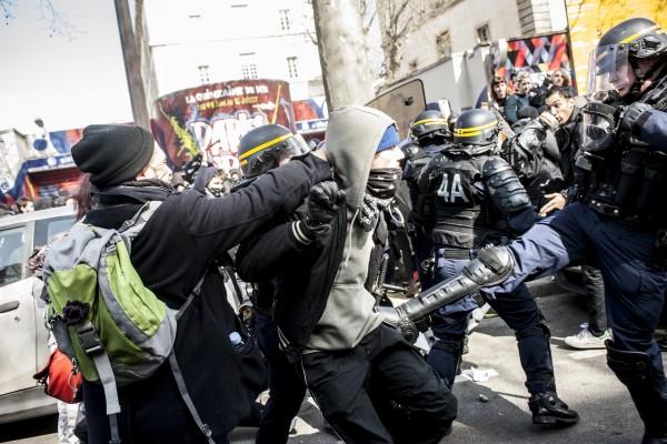 Un policer assène un coup de pied à un manifestant demandant la libération de ses camarades pris dans la nasse.