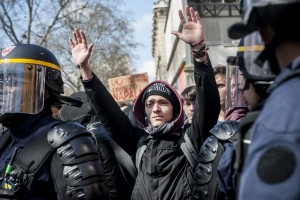 Un lycéen dans une nasse lève les bras en signe de non violence.