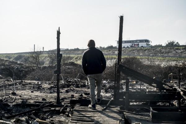 Le démantèlement de la zone sud de la jungle de Calais arrive à sa fin. Un réfugié observe la route sur les cendres d'un ancien restaurant de la jungle.