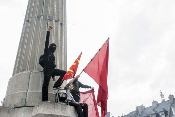 Un manifestant grimpe sur la colonne de la Déesse le poing levé vers la foule