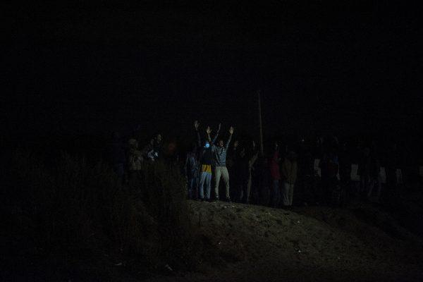 Des réfugiés lèvent les bras en signe de non violence. Ils seront tout de même gazés. Tous les soirs, des affrontements ont lieu autour de la jungle. La police utilise des gaz lacrymogènes et des canons à eau pour repousser les réfugiés dans la jungle.