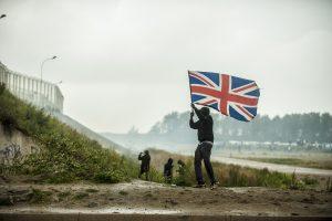 Manifestation en faveur des réfugiés. 1er octobre 2016 – Calais. Un réfugié se rapproche de la ligne de CRS drapeau britannique à la main. Pays vers lequel les réfugiés demandent l'ouverture des frontières.