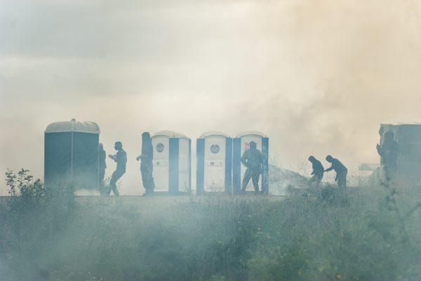 Manifestation en faveur des réfugiés. 1er octobre 2016 – Calais. Les réfugiés se protègent des grenades et des tirs de LBD derrière les toilettes de l'entrée de la jungle.