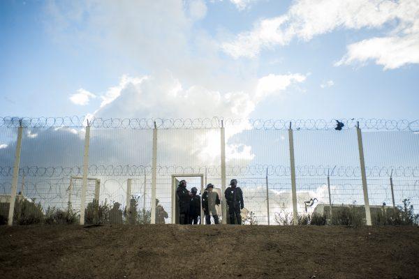 Manifestation en faveur des réfugiés. 1er octobre 2016 – Calais. D'autres policiers attendent le long du grillage qui protège la la rocade portuaire.