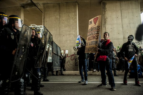 Manifestation en faveur des réfugiés. 1er octobre 2016 – Calais. Un soutien brandit une pancarte et jouera de la guitare tout à long du rassemblement