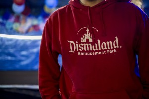 A man wearing a sweater DISMALAND created by Banksy. He gave migrants elements of ephemeral Bemusement park. In Calais, northern France, February 23, 2016