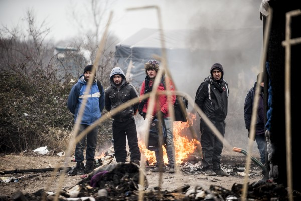 Des réfugiés de la zone sud de la jungle observent les ouvriers détruire leurs habitation.
