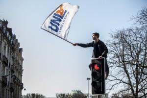 Un lycéen grimpe sur une feu tricolore et harangue la foule de lycéens drapeau à la main.