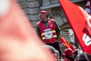 Un syndicaliste CGT porte autour du cou l'affiche contre les violences policières en France au cours des derniers mois.