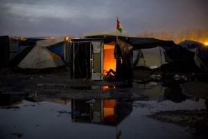 Un réfugié se repose autour d'un feu dans sa cabane de la zone nord de la Jungle de Calais.