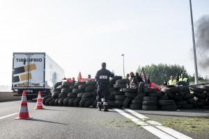 De l'essence est versée sur l'ensemble de la barricade suite à l'arrivée d'un quinzaine de policiers casqués.