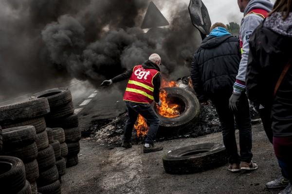 blocage devant le dépôt pétrolier de Douchy-les-Mines. Un syndicaliste de la CGT alimente le feu avec des pneus.
