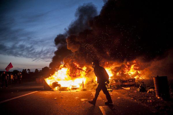 blocage devant le dépôt pétrolier de Douchy-les-Mines. Un manifestant traverse la route devant les barricades en feu.