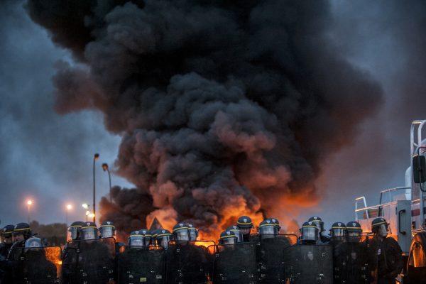 blocage devant le dépôt pétrolier de Douchy-les-Mines. La police arrive très tôt sur le blocage. Les manifestants mettent le feu aux barricades.  Un épais nuage de fumée se dégage de la barricade en feu.