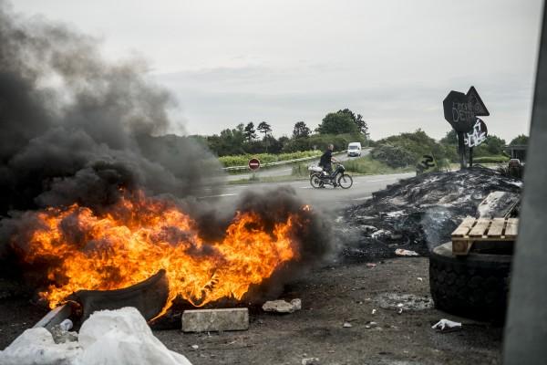 blocage devant le dépôt pétrolier de Douchy-les-Mines. Un jeune homme pousse sa mobylette, en panne d'essence.