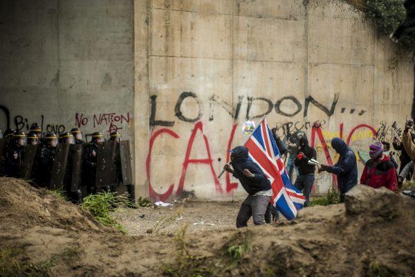 Manifestation en faveur des réfugiés. 1er octobre 2016 – Calais. Des réfugiés se rapprochent de la ligne de CRS drapeau britannique à la main. Pays vers lequel les réfugiés demandent l'ouverture des frontières.