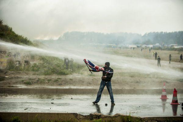 Manifestation en faveur des réfugiés. 1er octobre 2016 – Calais. Un réfugié tenant un drapeau britannique à la main est repoussé par le canon à eau