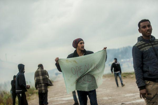 Manifestation en faveur des réfugiés. 1er octobre 2016 – Calais. Un réfugié tient un tissus sur lequel est inscrit «Open the UK border»