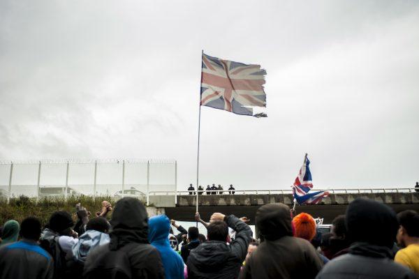 Manifestation en faveur des réfugiés. 1er octobre 2016 – Calais. Un drapeau britannique flotte au dessus du rassemblement. La plupart des réfugiés souhaitent rejoindre la Grande Bretagne.