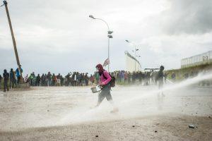 Manifestation en faveur des réfugiés. 1er octobre 2016 – Calais. Un musicien de la batucada est arrosé par la canon à eau. Quelques minutes plus tard, il sera arrêté par la police lors d'une charge.