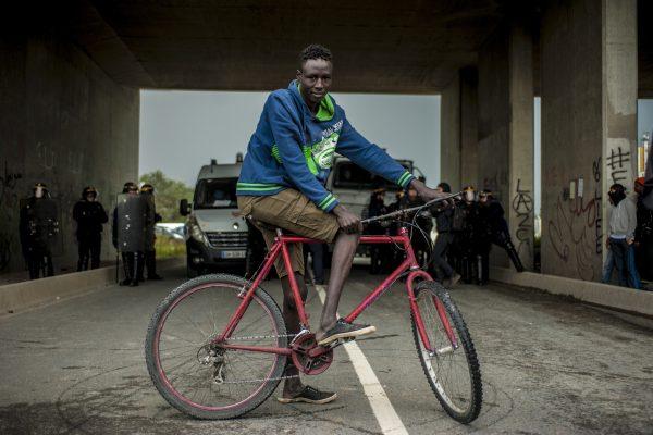 Manifestation en faveur des réfugiés. 1er octobre 2016 – Calais. Un jeune réfugié à vélo vient observer ce qu'il se passe.